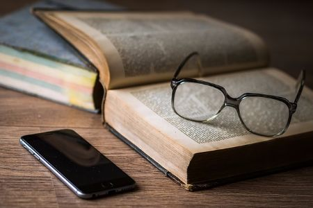hipster glasses and phone with old books